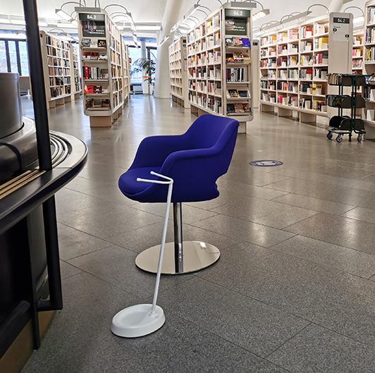YSTAND-kyynärsauvateline Tampereen Metso-kirjaston asiakaspalvelupisteen edessä. Vieressä kirkkaan sininen tuoli ja taustalla kirjastohyllyjä.