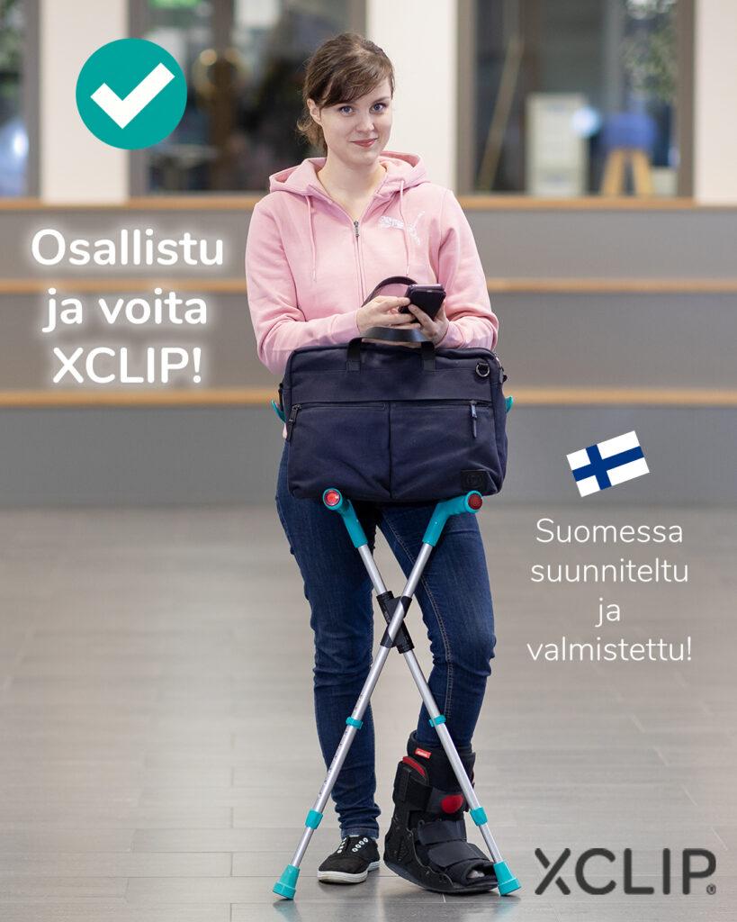 XCLIP-pidike käytössä kyynärsauvoissa Sauvat tukevasti pystyssä ja läppärilaukku kahvojen päällä. Tyytyväinen ilme nuorella naisella.