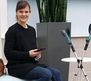 Nuori nainen hymyilee kuvaajalle kännykkä kädessä. Vieressä kyynärsauvat tukevasti pöytää vasten.