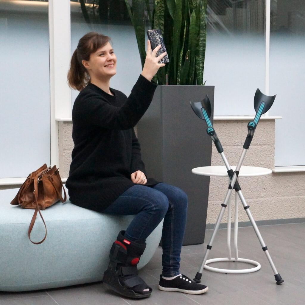 Nuori nainen istuu hymyillen penkillä ja ottaa selfietä. Kyynärsauvat ovat tukevasti pöytää vasten. Sauvat muodostavat tukevan X-muotoisen kokonaisuuden XCLIP-pidikkeen anaiosta.